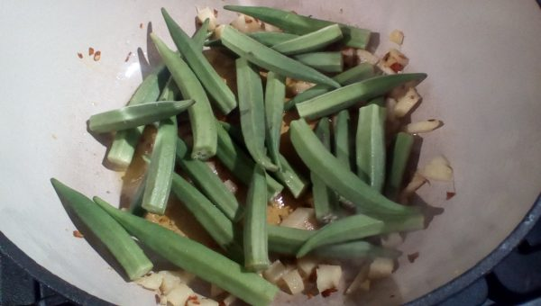 Once sizzling add half the Okra. Let that fry until it is gaining some colour then add the rest and stir in.